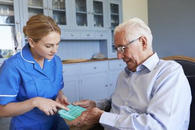 caregiver helping senior man for medication