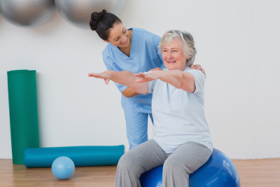 caregiver assisting senior woman for exercise routine